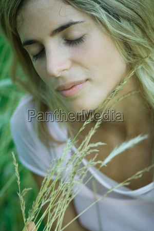 young woman holding tall grass eyes