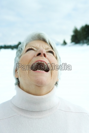 senior woman laughing in snowy landscape