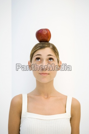 young woman with apple balanced on