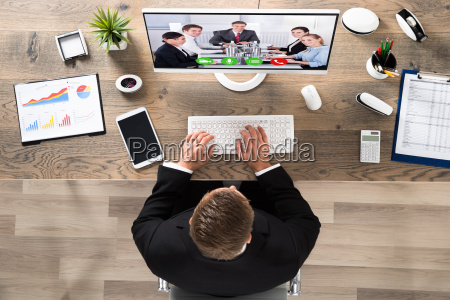 businessman attending video conference at office