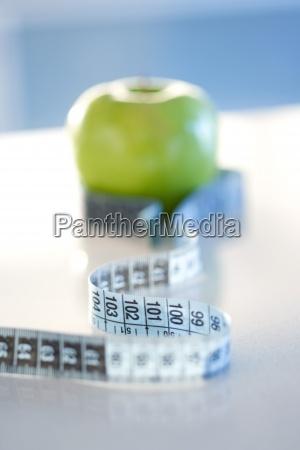 tasma pomiarowa owinieta wokol zielonego jablka