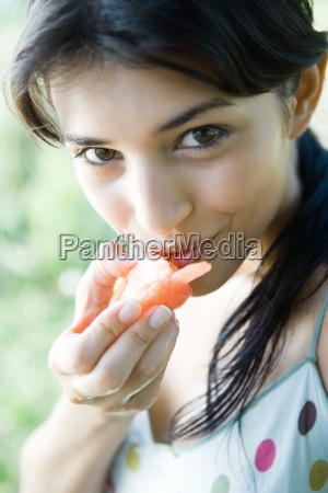 young woman eating chunk of fruit