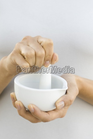 woman using mortar and pestle close