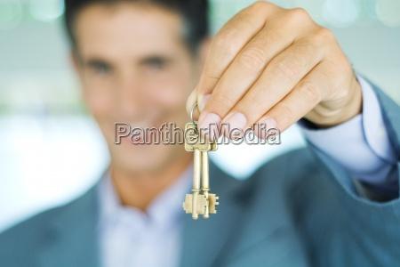 mezczyzna trzyma klucze w kostiumu ostrosc