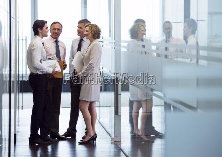 ludzie biznesu rozmawiaja w holu biura