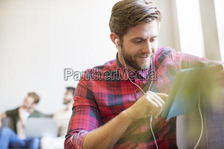 casual biznesmen z sluchawek i cyfrowym