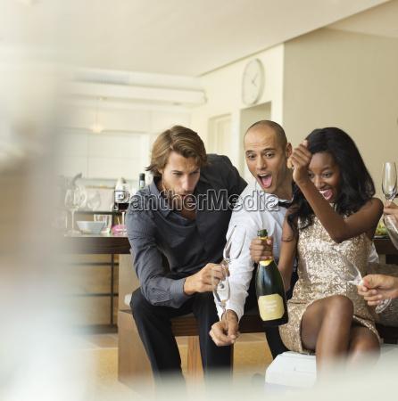znajomi otwierania butelki szampana razem