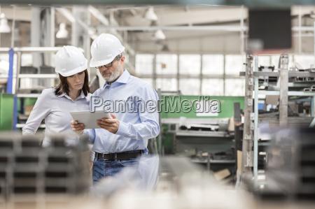 inzynierowie uzywajacy tabletu cyfrowego w fabryce