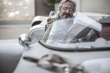 starszy czlowiek w samochodzie sportowym patrzac
