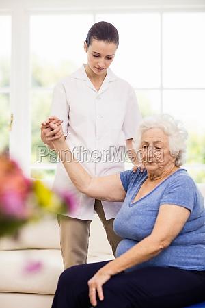 physiotherapist taking care of sick elderly