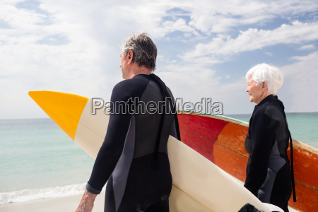 senior couple in wetsuit holding surfboard