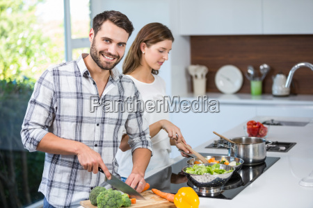 man helping woman in preparing food