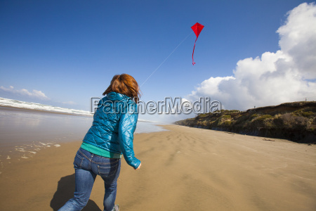 a young woman flys a red
