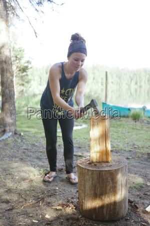 a young woman chops firewood with