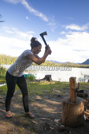a woman chops firewood with a
