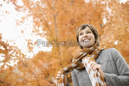 kobieta w plaszczu i szyi szalik