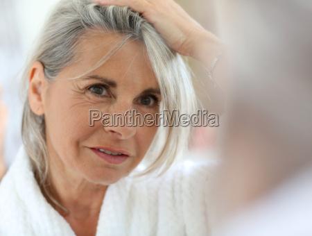 starszy kobieta martwi sie wlosy coraz