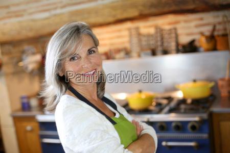 portret starszej kobiety w domowej kuchni