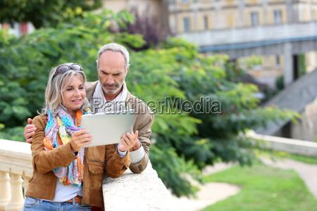 starsi turysci poszukuja informacji na tablecie