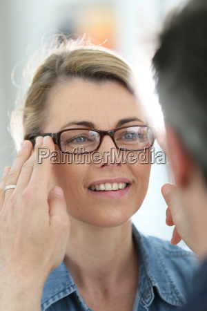 mature blond woman with optician trying