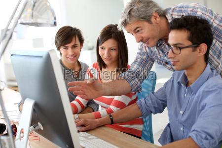 nauczyciel z uczniami pracujacych na pulpicie