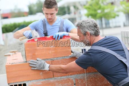 mason ze stazysta w budowie scianie
