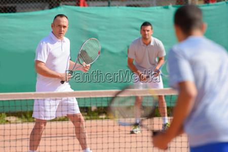 mezczyzni grajacy w tenisa podwaja
