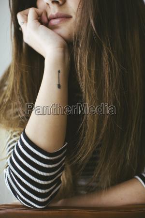 mloda kobieta ze strzalka tatoo na