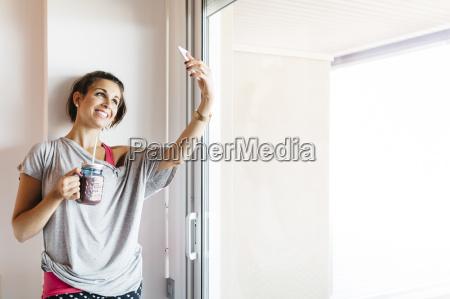 usmiechnieta mloda kobieta z zdrowym drinkiem