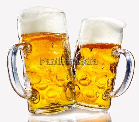dwa szklane kubki piwa pelne zlotej
