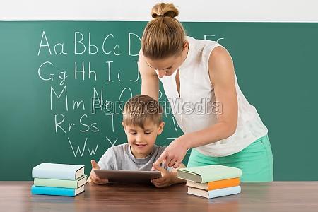 teacher with boy using digital tablet