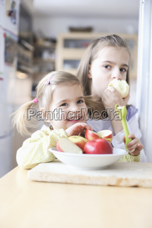 girls eating apples at table