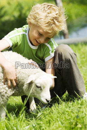 young boy sitting in grass petting