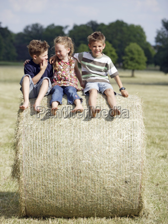 young children sitting on hay bale