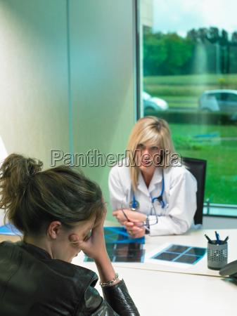 zaniepokojona kobieta lekarz przy biurku