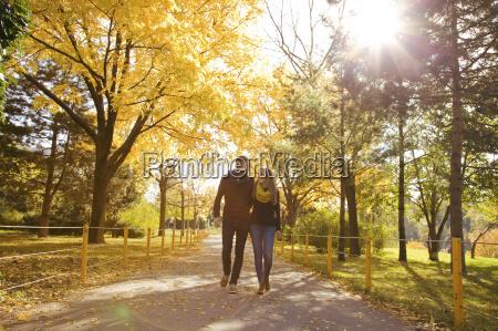 mloda para spacerujac w parku jesiennym