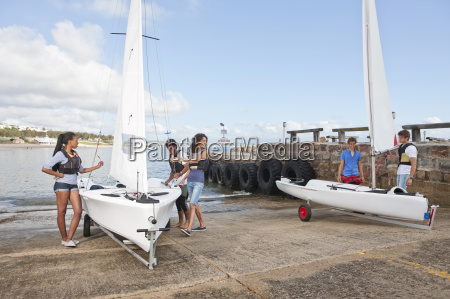 young adult friends preparing sailboats on