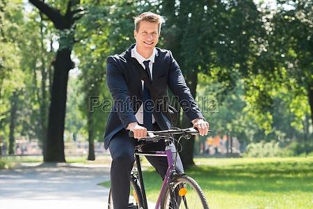 biznesmen jazda na rowerze w parku