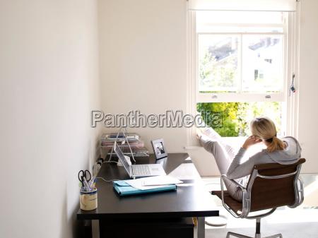 kobieta siedzi w domu sunny biura