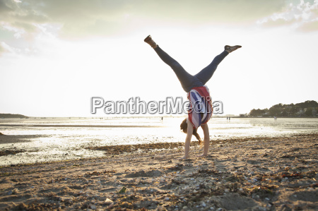 young woman doing handstand on bournemouth