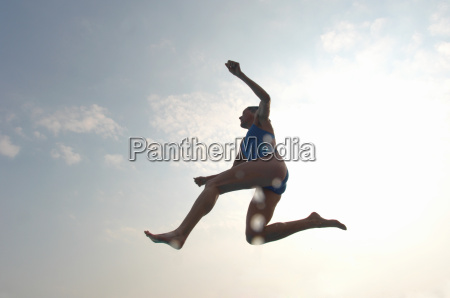woman wearing swimming costume jumping