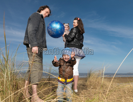 family at beach playing with ball