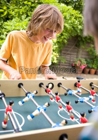 boy 10 12 playing table football