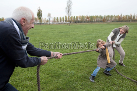 grandparents and girl playing tug of