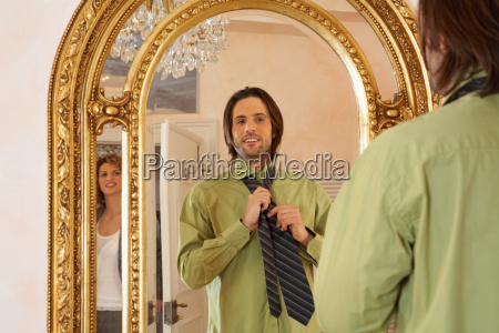 young man adjusting tie in mirror