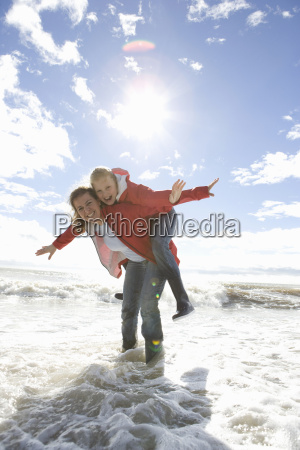 mom and daughter at beach piggyback
