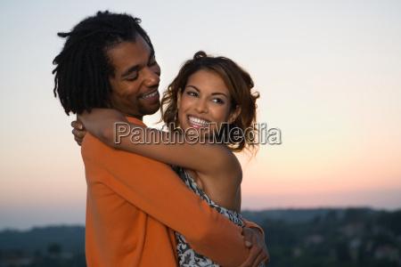young man and woman hugging at