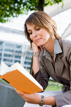 woman sitting outdoors reading book