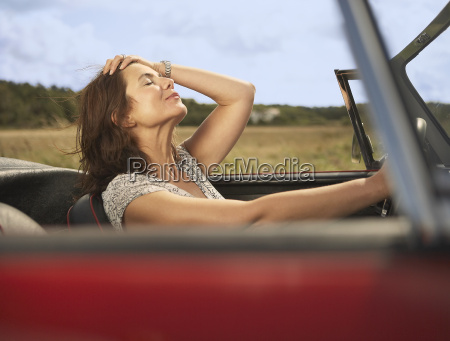 mid aged woman in sports car