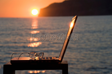 a laptop and reading glasses at